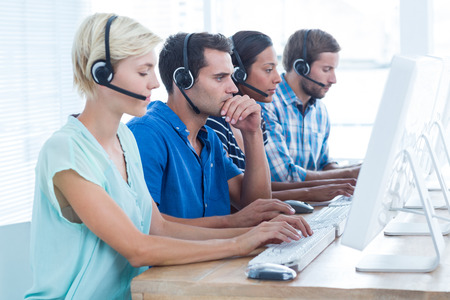 call center woman: Attentive call centre workers on their laptops Stock Photo
