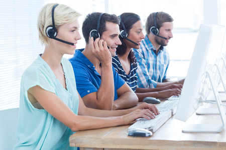 center agent: Happy call centre workers on their laptops