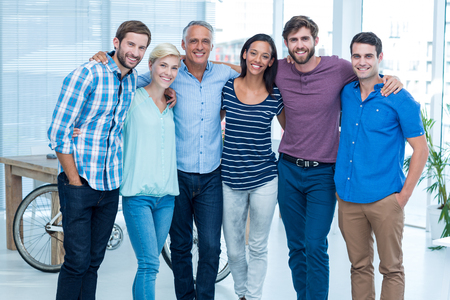 arms around: Portrait of a happy business team standing with arms around in the office Stock Photo
