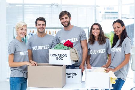 altruism: Retrato de voluntarios felices amigos que separan las materias de donación