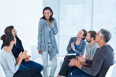 terapia de grupo: Aplaudiendo grupo Rehab deleit� mujer de pie en la sesi�n de terapia