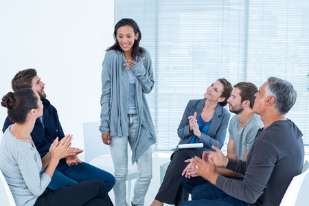 therapy group: Rehab group applauding delighted woman standing up at therapy session