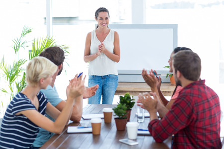 Young business team clapping hands in a meeting Stock Photo