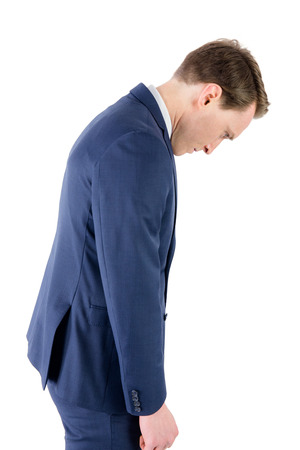 defeated: Defeated businessman looking down on white background Stock Photo