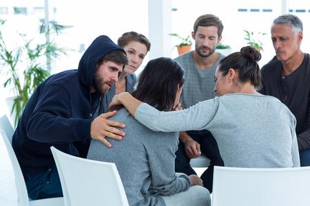 terapia grupal: Preocupados pacientes reconfortante otro en el grupo de rehabilitación en una sesión de terapia