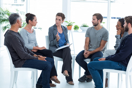 round chairs: Group therapy in session sitting in a circle in a bright room Stock Photo