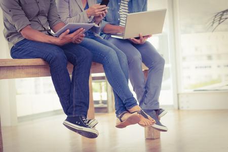 tvůrčí: Tři tvůrčí obchodní tým pracující na elektronických zařízení v kanceláři Reklamní fotografie