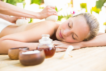 alternative wellness: Attractive young woman getting massage on her back at spa center
