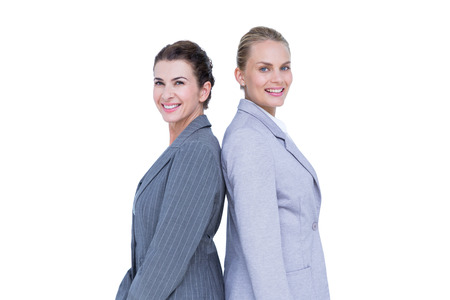 against white: Attractive businesswomen standing back-to-back against white wall