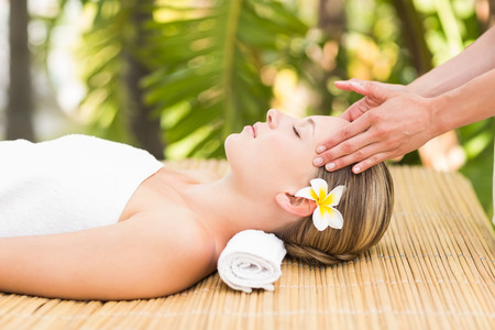 vida sana: Close up de una atractiva joven que recibe masaje facial en el spa