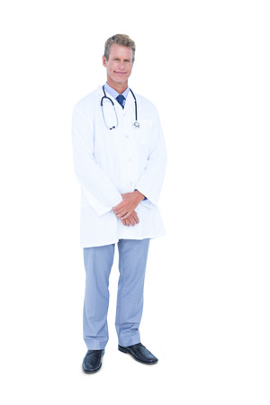 standing against: Male doctor standing against a white background Stock Photo
