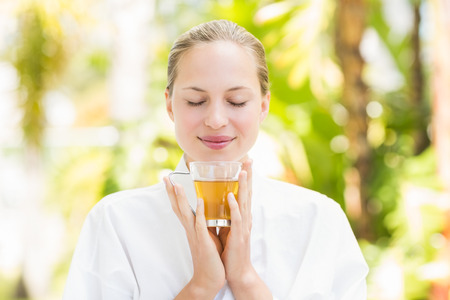 drinking tea: Attractive woman drinking tea in a glass at spa center