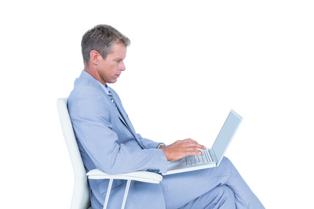 swivel: Handsome businessman sitting on a swivel chair and using his laptop against a white screen