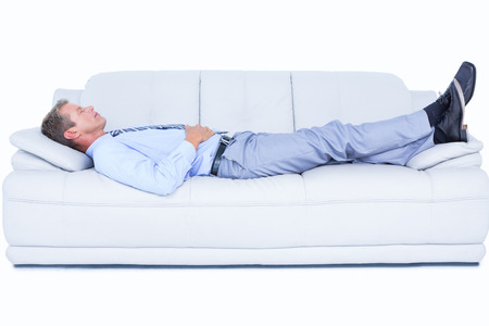 Tired businessman lying on the sofa against white screen