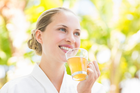Attractive woman drinking tea in a glass at spa center