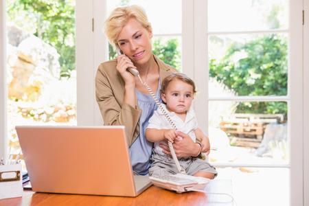madre trabajadora: Mujer rubia bonita con su hijo telefona y que usa la computadora portátil en la oficina Foto de archivo