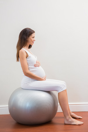 exercice: Happy pregnancy sitting on exercice ball on room Stock Photo