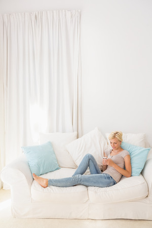 sofa: appy blonde woman using her mobile on the sofa at home in the living room Stock Photo