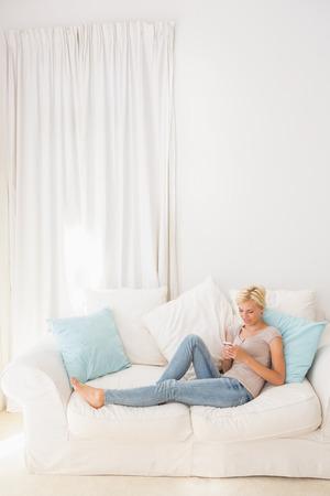 rubia: Appy mujer rubia que usa su móvil en el sofá en casa en la sala de estar