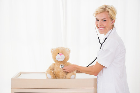 paediatrician: Smiling bonde doctor with stethoscope in the teddy bear in th medical office