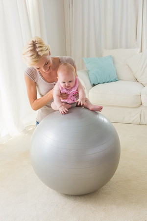 exercice: Happy mother with her baby girl on the exercice ball at home in the living room