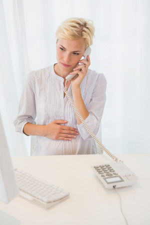 Smiling blonde woman using computer and phoning in the office Stock Photo
