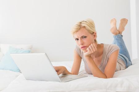 typing: Mujer rubia seria usando la computadora portátil en casa en el dormitorio Foto de archivo