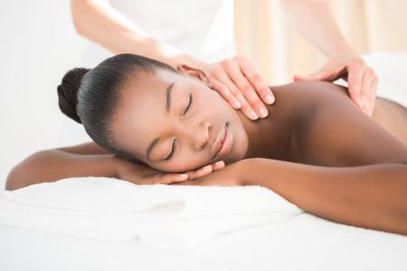 Pretty woman freut sich bei einer Massage im Wellnessbereich