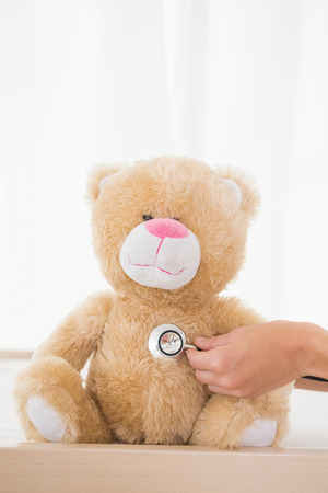 paediatrician: Teddy bear with doctor and stethoscope in the medical office