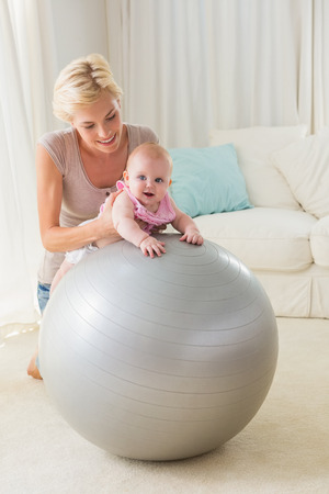 exercice: Happy mother with her baby girl in the exercice ball at home in the living room Stock Photo