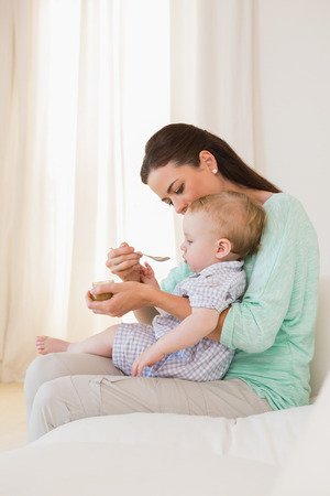 baby love: Happy mother eating with her baby boy at home in bedroom