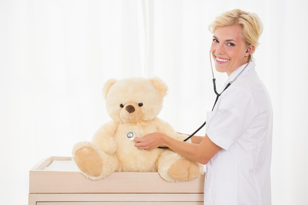 paediatrics: Portrait of a blonde doctor with stethoscope and teddy bear in the medical office
