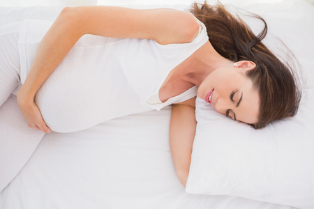 vientre femenino: Pregancy feliz se alarga en la cama en su casa en el dormitorio