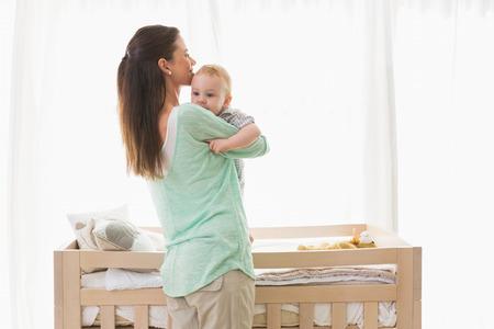 madre e hijo: Madre feliz con su bebé en su casa en el dormitorio