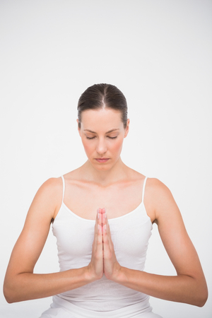 mani incrociate: Fit woman meditating with hands crossed on white background