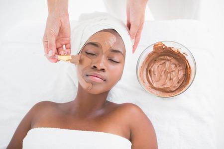 masaje facial: Mujer bonita que consigue un tratamiento facial de chocolate en el centro de rehabilitación