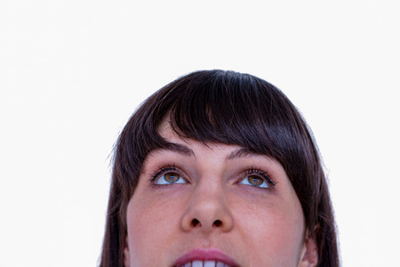 looking up: Close up of woman looking up on white background Stock Photo
