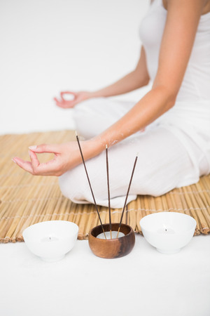 bamboo mat: Fit woman meditating on bamboo mat on white background