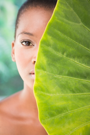 greenness: Portrait of a pretty woman looking through leaves on a greenness background