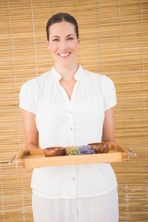 beauty therapist: Portrait of a smiling beauty therapist holding tray of beauty treatments at the spa Stock Photo