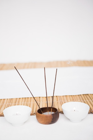 bamboo mat: Perfumed candles and incense stem nearby a bamboo mat