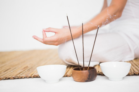 女性の白い背景の竹マットに瞑想に合わせて 写真素材