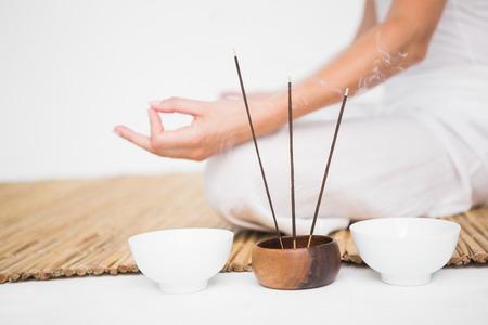 Fit vrouw mediteren op bamboe mat op een witte achtergrond