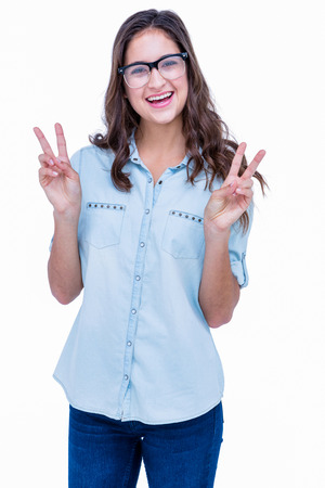 geeky: Pretty geeky hipster making peace sign on white background