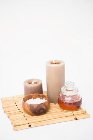 perfumed: Perfumed candles and beauty products on a bamboo mat Stock Photo