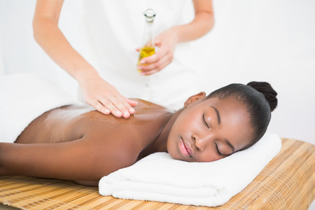 masseuse: Masseuse pouring massage oil on a pretty woman back at the health spa