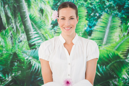 Portrait of a smiling beauty therapist holding a towel at the spa Stock Photo