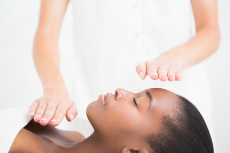 chakra: Pretty woman enjoying a reiki technique at the health spa