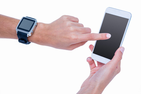 scrolling: Close up of woman using her smartphone and wearing smartwatch on white background Stock Photo