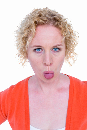 grimacing: Blonde woman grimacing in front of camera on white background Stock Photo